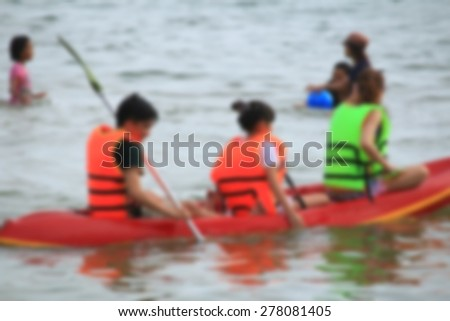 blurred people play boat rubber at sea