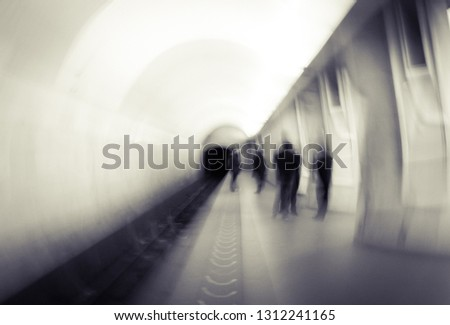 Blurred people waiting for a train on a platform. Passengers in a subway. #1312241165