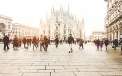 Blurred people walking in front of Duomo square in Milan - Defocused crowd on italian metropolis center - City lifestyle and tourism destination concept - Focus on cathedral church