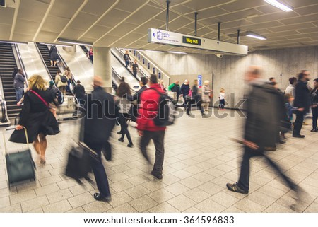 Blurred people walking inside train station or airport, with luggage and bags. There are some escalators on background, with people walking on both directions. Travel and urban lifestyle concepts.