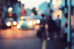 Blurred people walking through a city street
