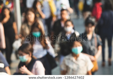 Blurred people wearing mask against air smog pollution with PM 2.5 in Bangkok city, Thailand.