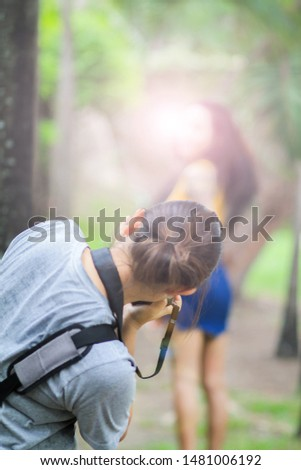 blurred photo,A photographer is photographing a model posing for a photo shoot in the park in the morning for a soft, beautiful light. The concept of professional photographers who love photography
