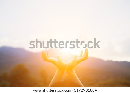 blurred photo,A young man prayed for God's blessings with the power and holiness of God on the background of the morning sunrise over the golden meadow. God and Spiritual Concepts.