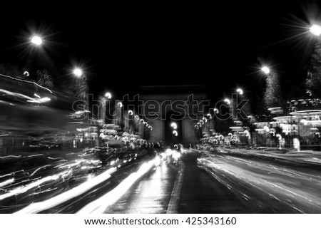 Blurred  photo of Arch of Triumph and Champs Elysees with Christmas festive illumination. Paris in winter. Blurred cars in motion. Black and white.