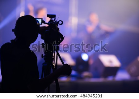 Blurred photo of Cameraman silhouette on a concert stage