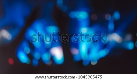Blurred photo of Christian worship God together in Church hall in front of music stage and light bokeh effected.raised hand and praise the LORD.Music concert background.