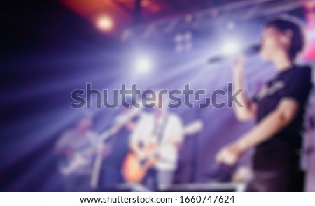 Blurred photo of Christian worship God together in Church hall in front of music stage.raised hand and praise the LORD.Music team concert background.Worshiper and worship team in Church.Concert image.