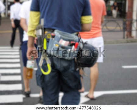 Blurred photo of construction worker with tool belt and helmet   - Shutterstock ID 477548026