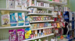 Blurred photo of dog food cat food and a lot of pet glooming products on the shelf in pet store in Bangkok, Thailand, under concept of business related to pet shop or veterinary clinic retail business