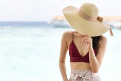 Blurred photo of Happy young girl at the sea. Lady in a hat at sea. Blur girl on beach in sunny day. Blur image of Asian girl stand by the beach with blue sky. Young adult Asian woman on vacation.