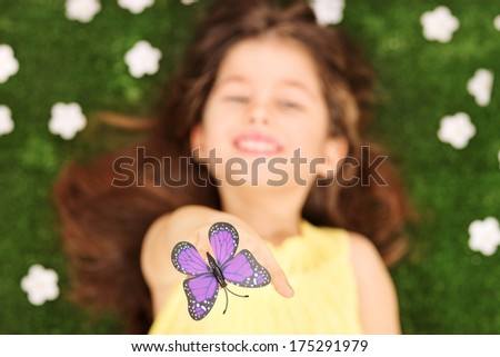 Blurred photo of little girl laying in meadow with flowers and reaching her hand to touch a purple butterfly