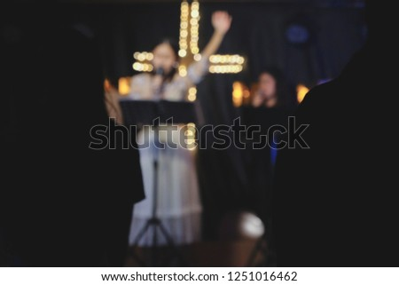 blurred photo of Women sing worship songs in church #1251016462