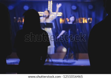 blurred photo of Women sing worship songs in church #1251016465