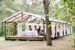 Blurred photo of wooden tent restaurant with wooden tables and chairs., decorated with light bulbs Vintage design of the restaurant in the forest in summer. Wedding reception in the open air.