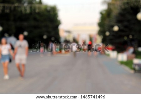Blurred photo. People stroll through the park on an evening summer evening. #1465741496