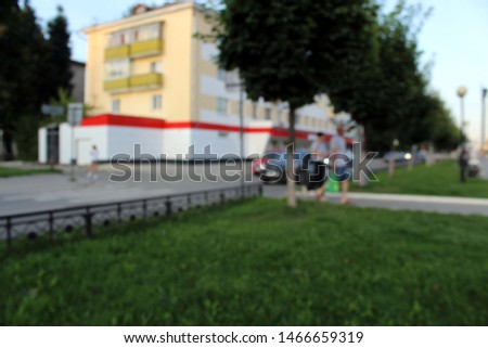 Blurred photo. People stroll through the park on an evening summer evening. #1466659319