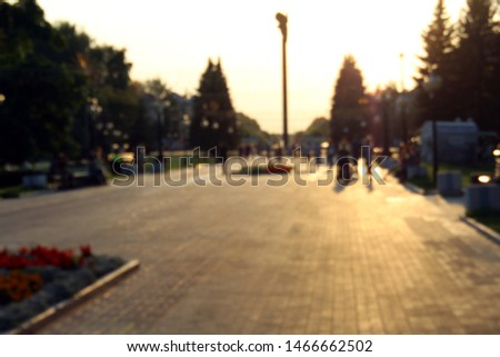Blurred photo. People stroll through the park on an evening summer evening. #1466662502