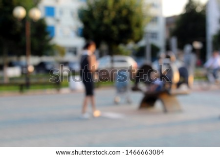 Blurred photo. People stroll through the park on an evening summer evening. #1466663084