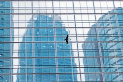 Blurred photo with motion blur of large bird flies along the glass wall of a skyscraper.  Bird flying over city