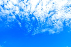 Blurred photography of beautiful fluffy altocumulus cloud in the blue sky in the afternoon. Skyscape and cloudscape in summer afternoon. Natural absrtact sky background with empty space for copy text.