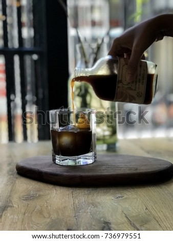 Blurred pic,abstract and back light of drip cold brew coffee on the wooden table in cafe,dark tone and black shadow