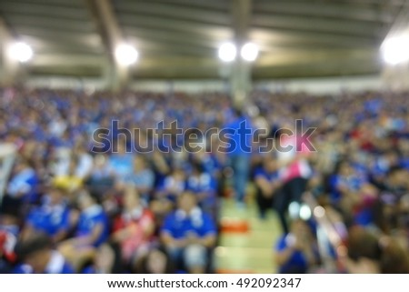 Blurred picture for background use :View of people are watching football sport in stadium .