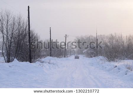 Blurred picture of a car on a snowy winter road in the snowfall
