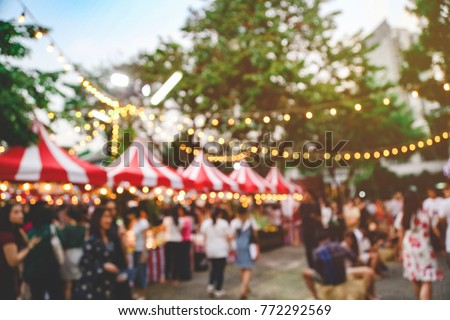 Blurred picture of Christmas festival in the park fullfill with crowd and lots of stalls for shopping with the hanging light bokeh and colorful twilight time background.