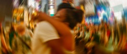 Blurred picture of happy couple embracing among Times Square night lights - New York City.