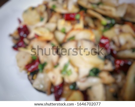 Blurred picture of mushroom food stir fried with garlic and dried chilies on a white plate. ストックフォト ©