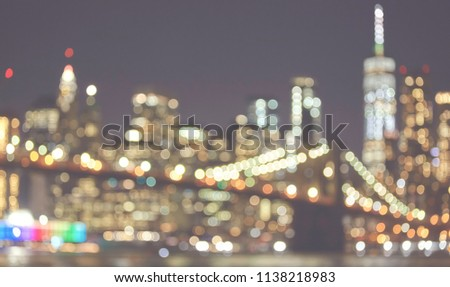 Blurred picture of New York City skyline at night, color toned picture, urban abstract background.