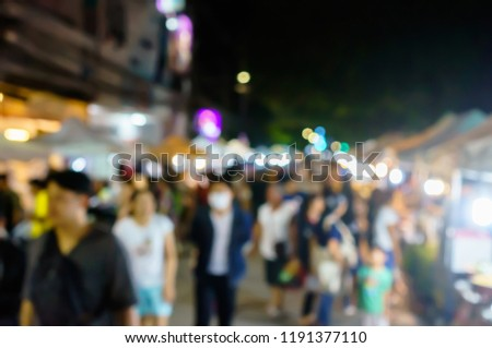 Blurred picture of people walking on night walking street, Chiang Rai, Thailand.