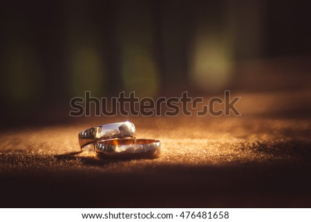 Blurred picture of sparkling wedding rings lying on the brown cloth