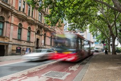 blurred red bus and car on one of the sydney streets during the day