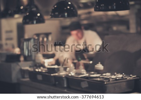 Blurred Restaurant chef: Chef cooking in the open kitchen, customer can see they cooking at food counter