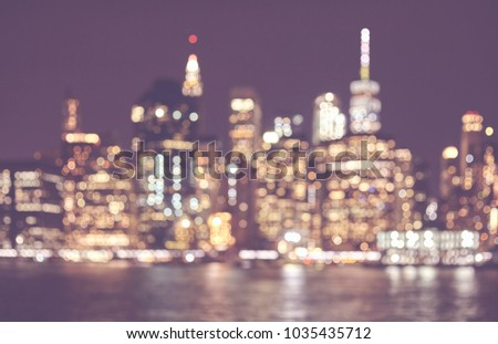 Blurred retro toned picture of Manhattan skyline at night, abstract urban background, New York City, USA.