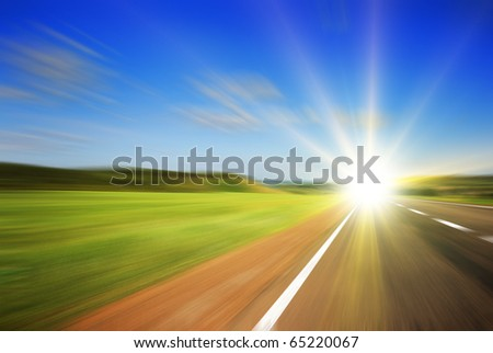 Blurred road and blue blurred sky with a shining sun