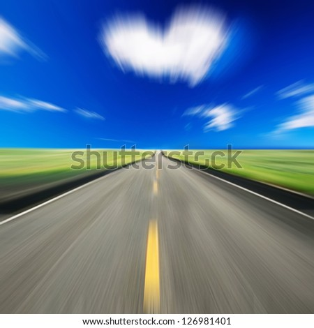 Blurred road and blue motion blurred sky with  heart shape cloud