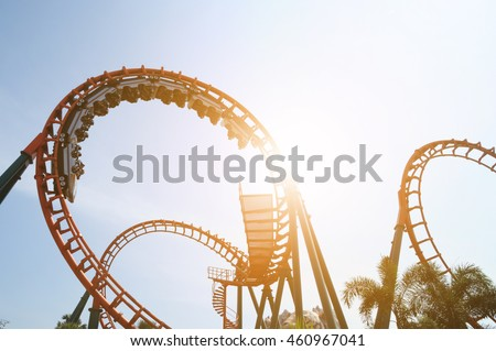 blurred Roller coaster ride in amusement park at evening, low key