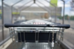 Blurred Row of shopping carts from behind. Black handle and chain. Shopping mall in the background. Rear view. All out of focus.