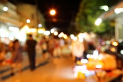 Blurred scene of tourists walk in night market.