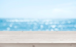 Blurred sea background with wood resort deck floor foreground