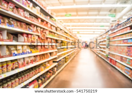 Blurred selection of pasta, ketchup, condiment, tomato sauce and canned vegetable on shelves in store at Humble, Texas, US. Aisle, row variety products, defocused background, bokeh light supermarket.