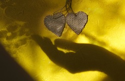 Blurred shadow of female hand and two wooden heart on rough yellow wall background. Sunlight and  crossed lines shadows, Minimal aesthetics. Abstract, play of light and shadow, shadow play illusion