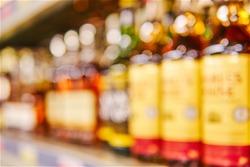 Blurred shelf with bottles of elite alcoholic beverages in large grocery supermarket. Basic background for design
