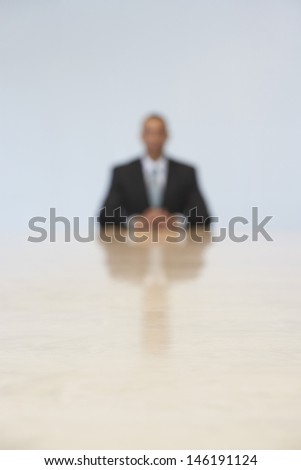 Blurred shot of a businessman sitting at the end of conference table in office
