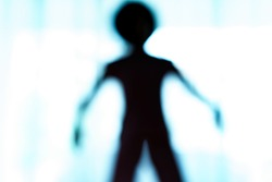 Blurred silhouette of human body look like alien.
