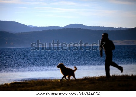 blurred silhouette of man and dog playing near high mountain lake