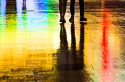 Blurred silhouette of people walking at night on the wet street.